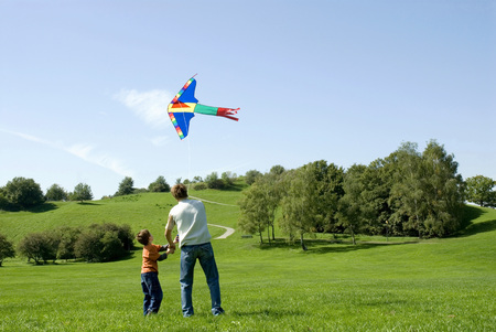kite flying: Father and son flying a kite, rear view
