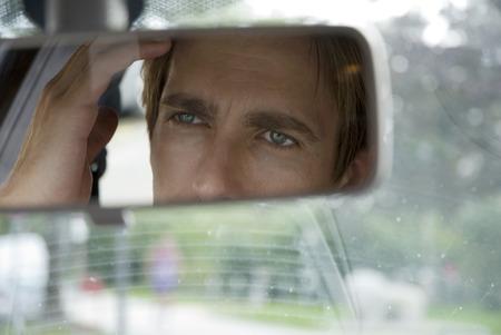 rear view mirror: El hombre joven que mira en el espejo retrovisor