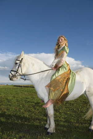Girl dressed as princess riding horse