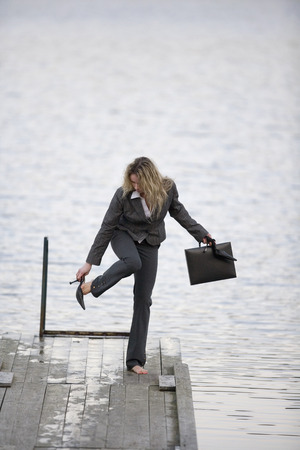 shoes off: Businesswoman standing on jetty, taking off shoes Stock Photo