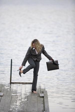 personas tomando agua: Empresaria que se coloca en el embarcadero, que saca los zapatos