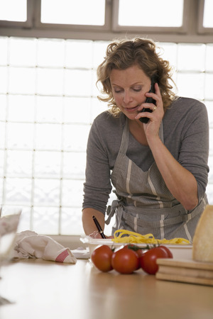 Mature woman standing in kitchen cooking and using mobile phone photo