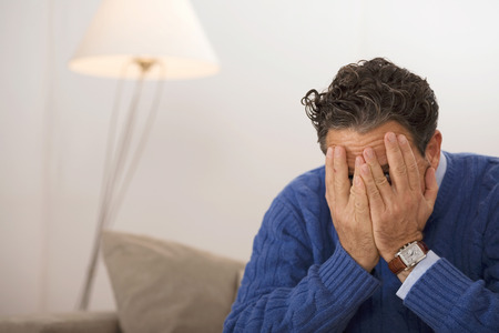 obscuring: Man sitting on sofa, face covered by hands Stock Photo