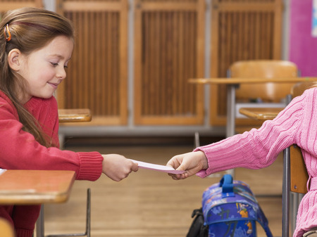 misbehaving: Girls exchanging notes in classroom Stock Photo