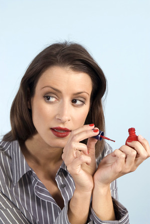 reluctance: Woman in office applying nail polish