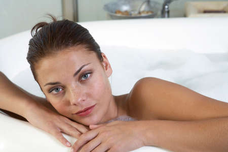 lying in bathtub: Young woman lying in bathtub