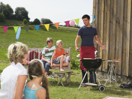 barbecuing: Family in garden having barbecue