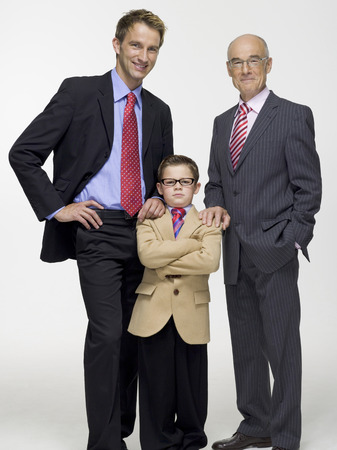 successor: Boy standing in business attire with father and grandfather