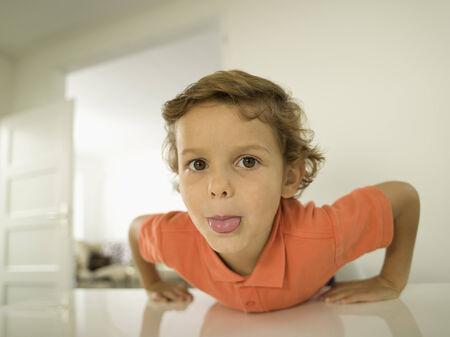 sticking out the tongue: Muchacho joven que mira a la c�mara sacar la lengua