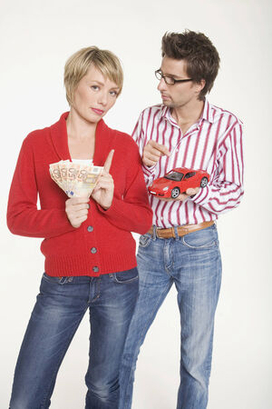 Young couple with money and toy car photo
