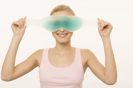 eyes close up: Adorable young woman wearing gel eye mask smiling