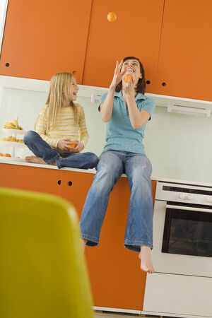Mother and daughter in kitchen, mother juggling oranges photo
