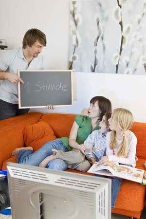 Family sitting on sofa in living room photo