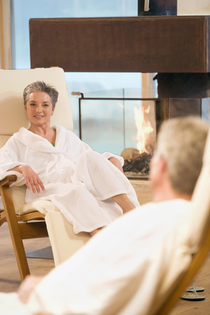 Mature couple in bathrobe sitting in deckchairs facing each other smiling photo