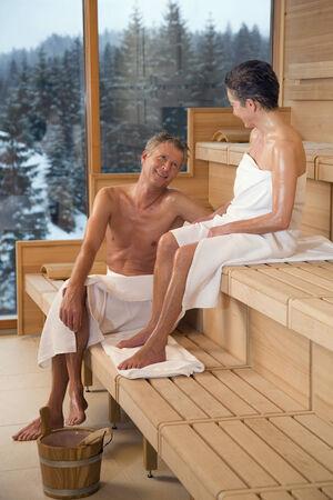 Älteres Paar sitzt in der Sauna Ansicht der verschneiten Wald