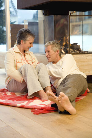 Mature couple sitting on blanket in front of fireplace  photo