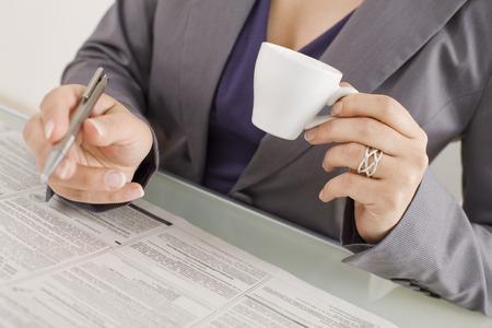 tomando refresco: Empresaria que toma notas con una taza de caf� de la secci�n media