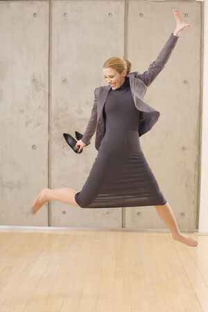 Joyful businesswoman jumping in the air photo