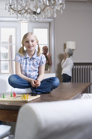 Girl sitting on tabletop smiling grandparents talking in background photo