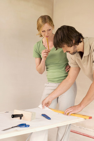 Young couple renovating cutting wallpaper photo
