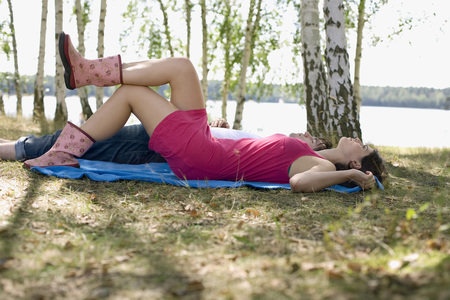 gumboots: Young couple relaxing on blanket in the forest by lake