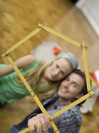 Junges Paar macht Haus Form mit klappbarer Regel Fokus auf Lineal