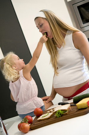 Pregnant mother and daughter in the kitchen eating photo