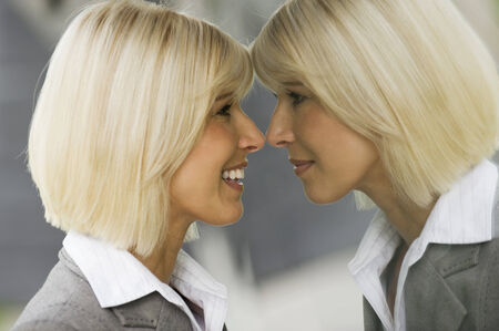 odd jobs: Blonde businesswoman smiling looking at mirror reflection