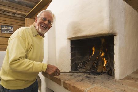 stoking: Senior man stoking fire in fireplace Stock Photo