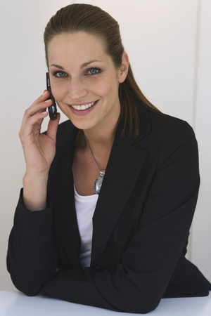 Business woman using mobile phone, smiling, portrait, close-up photo