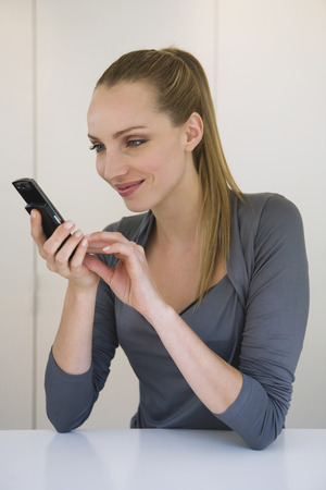 Business woman holding mobile phone, portrait photo