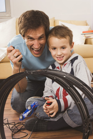 car race track: Father and son playing with toy car race track