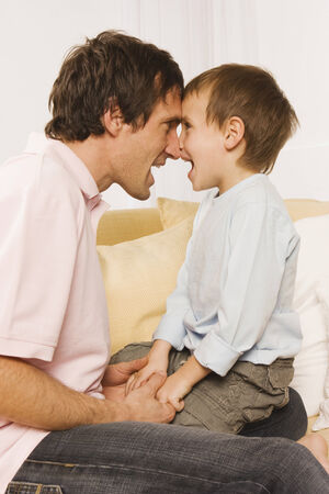 rubbing noses: Father and son fooling about rubbing nose together Stock Photo