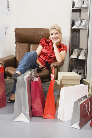 Young woman in shoe shop sitting in armchair smiling photo