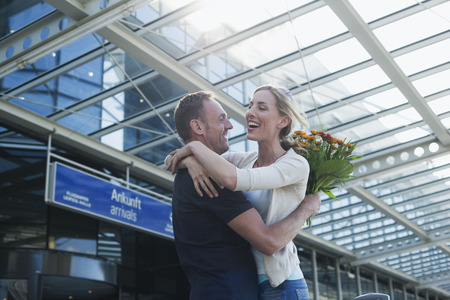 hugging couple: Germany, Leipzig-Halle, Airport, couple embracing man holding bunch of flowers