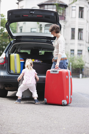Mother and daughter loading luggage into car photo