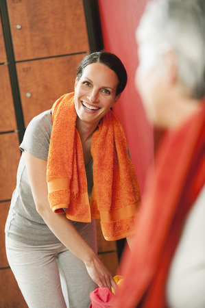 changing room: Two women in changing room towel round shoulders smiling