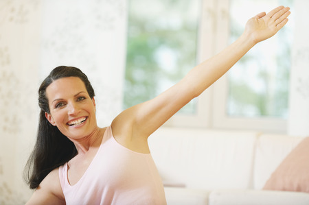 stretched out: Attractive young woman doing fitness exercise bending arm stretched out smiling Stock Photo