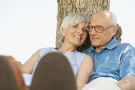 Spain Mallorca senior couple sitting by tree relaxing photo