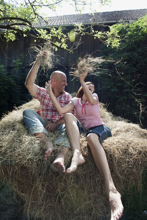 fooling: German Bavaria couple sitting on haystack fooling around throwing hay on each other