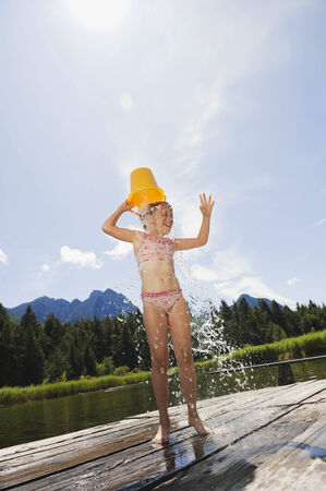 wet: Italy, South Tyrol, girl pouring a bucket of water over her head