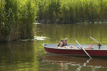 Italy, South Tyrol, Young couple lying in rowing boat photo