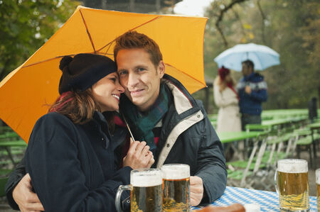 embracing couple: Alemania, Baviera, Jard�n Ingl�s, pareja sentada bajo el paraguas en la lluvia jard�n de la cerveza Foto de archivo