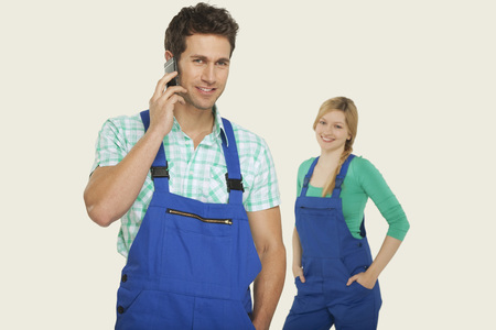 workwoman: Man in overall using mobile phone woman standing in background