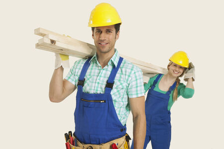 workwoman: Man and woman in overall and hardhat carrying timber smiling Stock Photo