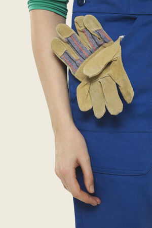workwoman: Woman in overall with gloves in pocket mid section close-up Stock Photo