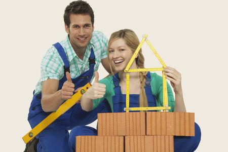 workwoman: Man and woman behind stack of bricks holding folding ruler and spirit level thumbs up