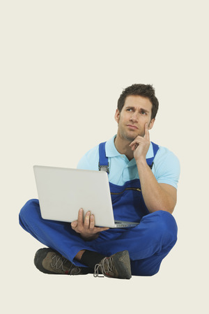 tailor seat: Man in overall sitting with laptop
