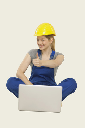 workwoman: Woman in overall sitting with laptop and showing thumbs up sign Stock Photo