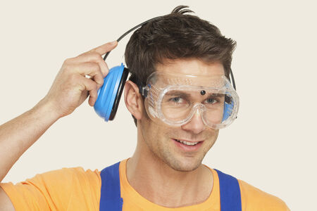 Man wearing ear muff and protective goggles smiling portrait photo